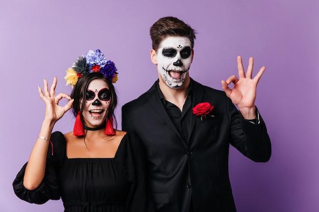 Lustige europäische junge leute, die in halloween herumalbern. innenaufnahme des lachenden liebespaares in zombiekleidung.