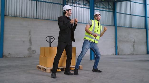 Lustige fabrikarbeiter tanzen in der fabrik. glückliche menschen bei der arbeit.