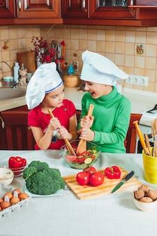 Lustige familienkinder bereiten den frischen gemüsesalat in der küche vor