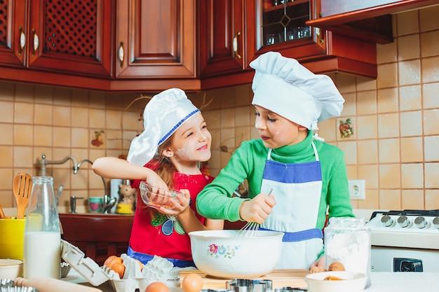 Lustige familienkinder bereiten den teig vor, backen kekse in der küche