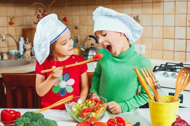 Lustige familienkinder bereiten einen frischen gemüsesalat in der küche vor
