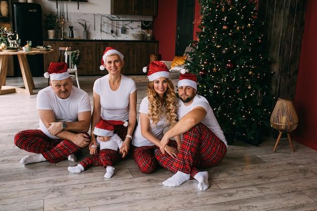 Lustige familienmitglieder mit einem kleinen baby in weihnachtsmützen und familienblick sitzen auf dem boden. weihnachtszeit.