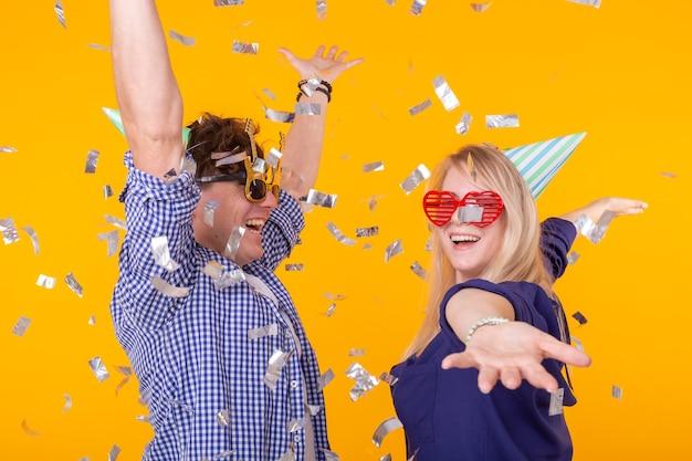 Lustige feiertage und partykonzeptpaar tanzen unter fallenden konfetti auf gelber wand