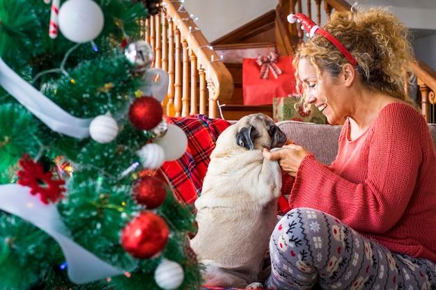 Lustige feiertagsweihnachtszeit mit alternativer erwachsener frau des paares und lustigem hundemops, die zusammen spaß auf dem sofa nahe dem weihnachtsbaum haben