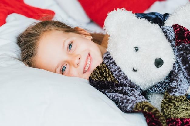 Lustige ferien in der kindheit. nettes kleines mädchen wachte im bett mit teddybärgeschenk auf und lächelte.