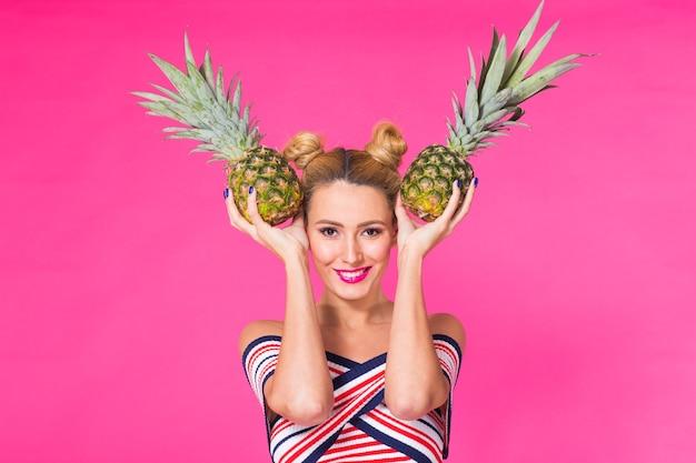 Lustige frau des modeporträts mit ananas über rosa hintergrund