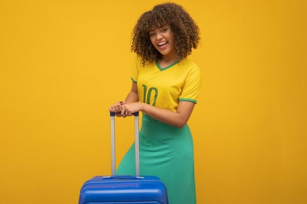 Lustige frau, die eine schwere reisetasche hält