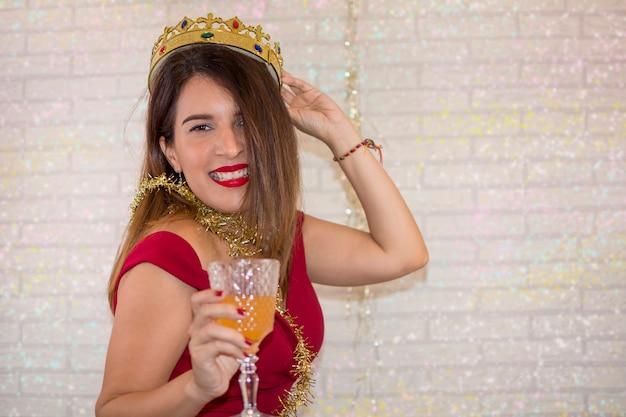 Lustige frau, die genießt, das neue jahr mit einer goldenen krone und einem glas champagner in ihrer hand zu feiern.