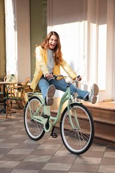 Lustige frau, die ihr fahrrad auf der straße reitet