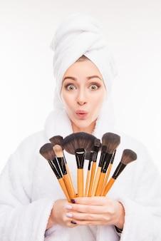 Lustige frau, die make-up-bürsten mit handtuch auf ihrem kopf hält