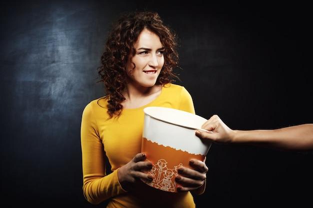 Lustige frau, die mit freunden nach popcorn strebt, während sie film sieht