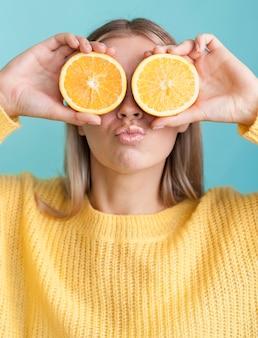 Lustige frau, die orangen hält
