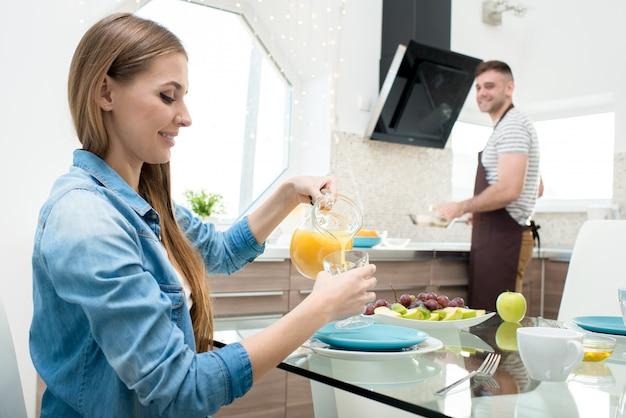 Lustige frau, die saft gießt, während mann frühstück kocht