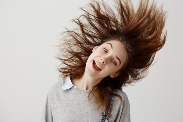 Lustige frau im pullover herumalbern und schüttelt den kopf mit schwebenden haaren. freudiger weiblicher musikliebhaber, der lieblingsmelodietanz hört, der spaß auf der party hat.