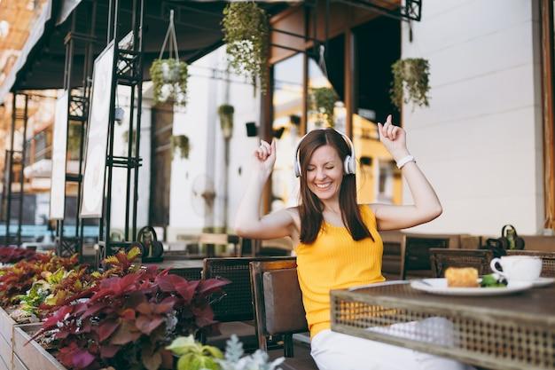 Lustige frau im straßencafé im freien, die in gelber kleidung am tisch sitzt und musik in kopfhörern hört