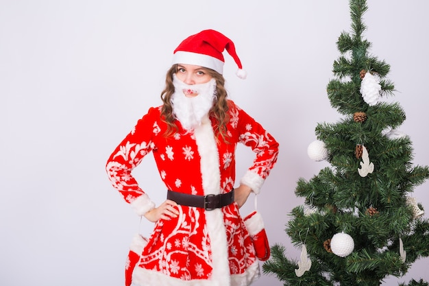 Lustige frau im tragen des weihnachtsmannkostüms über weihnachtsbaum