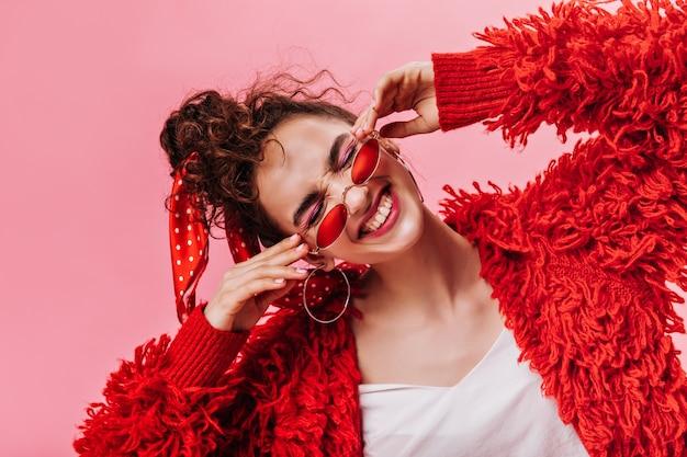 Lustige frau in der roten flauschigen jacke, die auf rosa hintergrund lacht