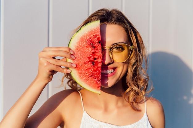 Lustige frau in der sonnenbrille, die eine hälfte ihres gesichtes mit stück wassermelone versteckt