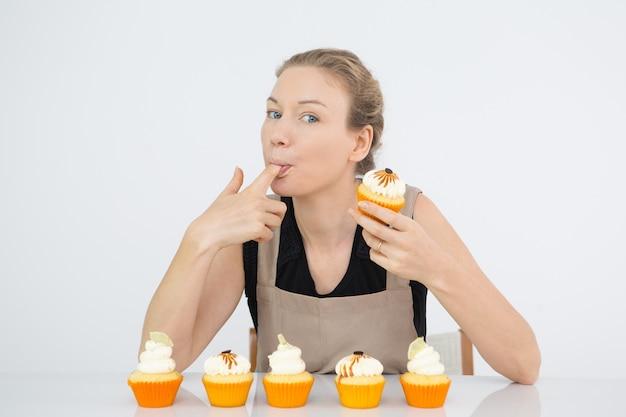 Lustige frau leckt finger mit buttercreme
