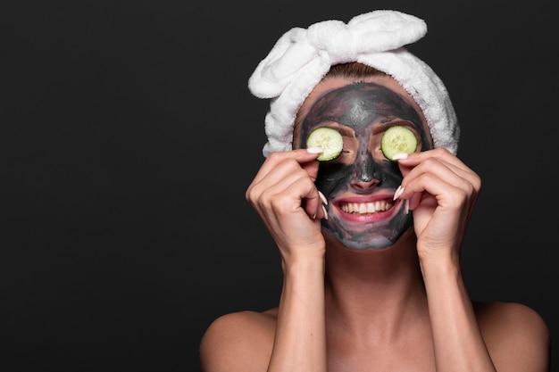 Lustige frau mit gesichtsmaskenbehandlung