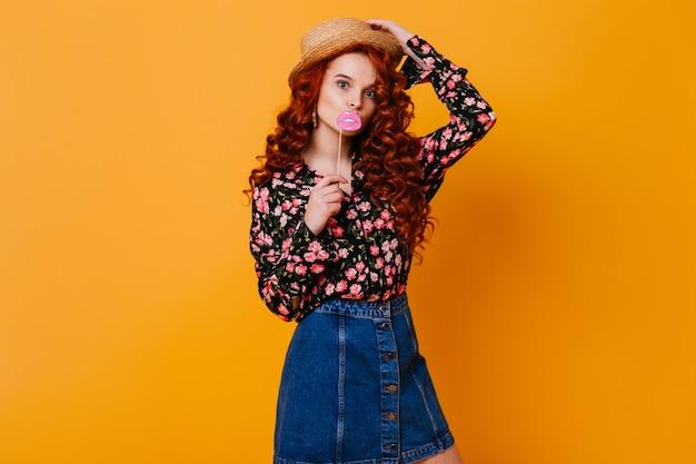 Lustige frau mit gewelltem rotem haar wirft mit spielzeugpapierlippen auf stock auf. mädchen im jeansrock und im oberteil hält hut auf orange raum.