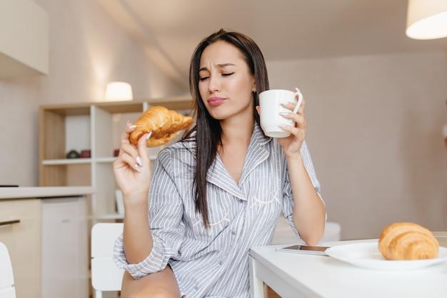 Lustige frau mit glattem schwarzen haar, das croissant während des frühstücks in den gemütlichen wohnungen isst