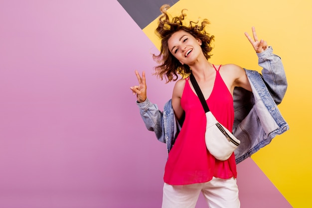 Lustige frau mit kurzen gewellten haaren, die tanzen und spaß auf mehrfarben haben.