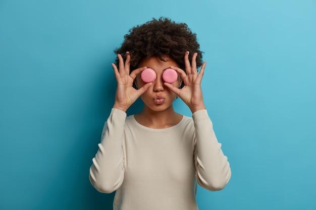 Lustige frau naschkatzen macht gläser aus zwei rosa makronen, hält die lippen rund, genießt es, kalorienreiche französische dessert zu essen, freut sich, diät zu brechen, hat spaß isoliert an der blauen wand. junk-food-konzept