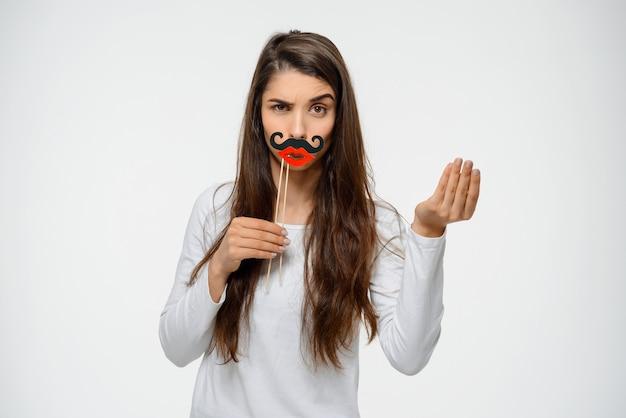 Lustige frau verzieht das gesicht in falschem schnurrbart und lippen