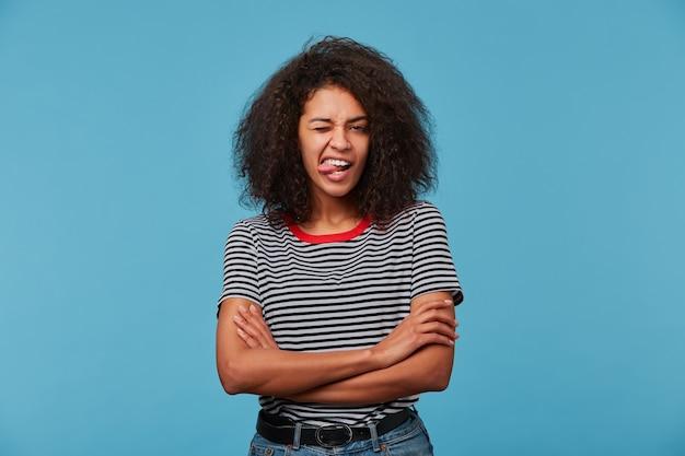 Lustige frau zeigt zunge, hat spielerischen ausdruck, afro-frisur, macht grimasse, gekleidet in abgestreiftem t-shirt
