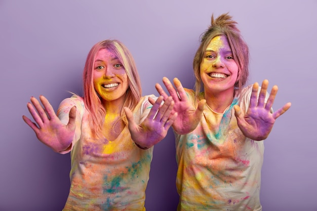 Lustige frauen feiern holi-feiertage, tragen weiße kleidung mit deutlich sichtbarem farbspray, zeigen beide mit mehrfarbigem puder verschmierten handflächen, amüsieren sich, verwenden bunte farbstoffe. ankunft des frühlings