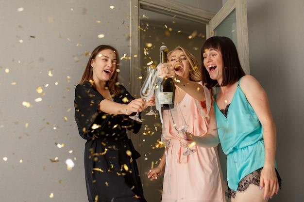 Lustige frauen machen toast mit champagnergläsern auf der junggesellenparty
