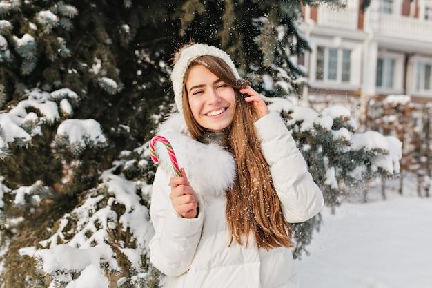Lustige freudige junge frau mit lollypop in der winterstadt. tolle stimmung, warme kleidung, fallender schnee, strahlende gefühle, ausdruck, neujahr und weihnachtszeit