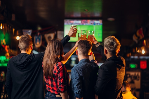 Lustige freunde schauen fußball im fernsehen und heben ihre gläser mit bier in einer sportbar, glückliche fans, feier des sieges im spiel