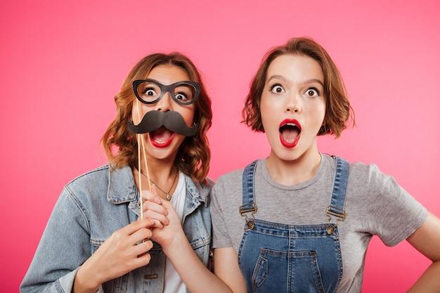 Lustige freundinnen, die gefälschten schnurrbart und gläser halten.