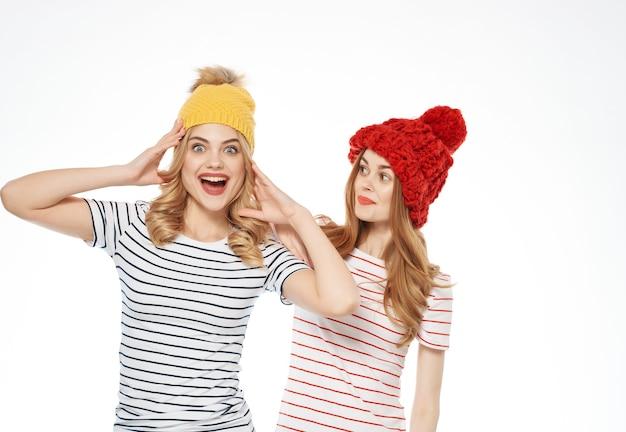 Lustige freundinnen mit hut stehen neben dem moda studio lifestyle