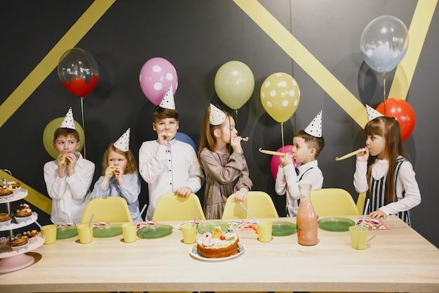 Lustige geburtstagsfeier für kinder im dekorierten raum. glückliche kinder mit kuchen und ballons.