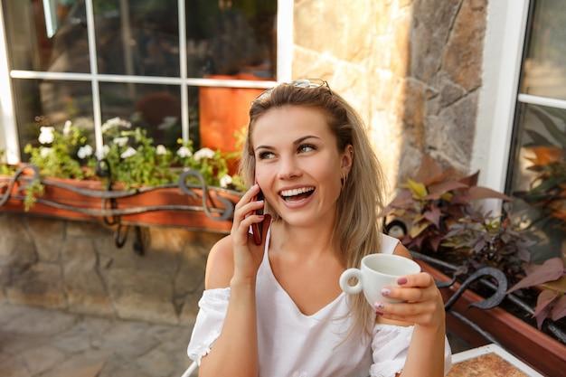 Lustige geschäftsfrau mit tasse kaffee, die an einem laptop arbeitet, draußen