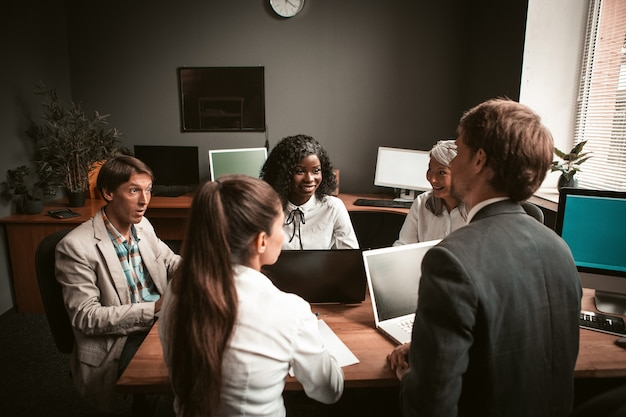 Lustige geschäftstreffengruppe der jungen multiethnischen geschäftsleute, die im modernen büro arbeiten