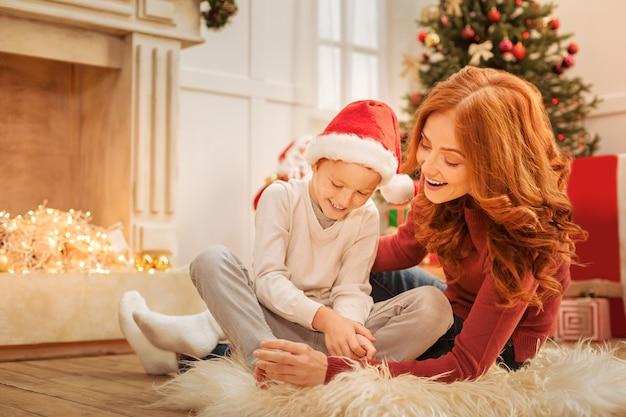 Lustige geschichten. harmonische familie, die breit grinst, während sie sich auf einem flauschigen teppich entspannt und während eines weihnachts-familiengesprächs scherzt.