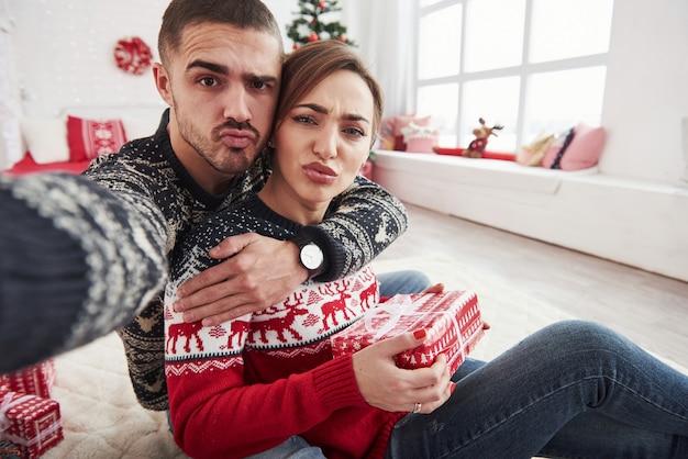 Lustige gesichter machen. mann, der selfie von ihm und seiner frau nimmt, die in der weihnachtskleidung gekleidet sind und auf dem boden des dekorativen schönen zimmers sitzen.