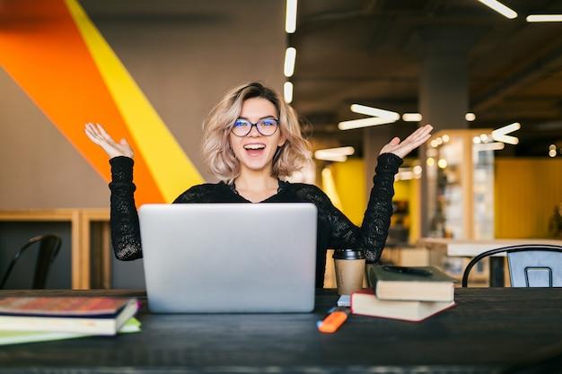 Lustige glückliche aufgeregte junge hübsche frau, die am tisch im schwarzen hemd sitzt und am laptop im mitarbeitenden büro arbeitet und brille trägt