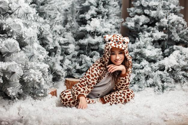 Lustige glückliche frau in einem trendigen bärenpyjama, der nahe einem weihnachtsbaum mit schnee im studio sitzt