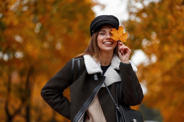 Lustige glückliche junge frau in der stilvollen oberbekleidung in einem schwarzen weinlesehut, der in einem park aufwirft. fröhliches mädchenmodell hält ein orange ahornblatt nahe gesicht und lächelt auf einem hintergrund von goldenem laub. herbsttag.
