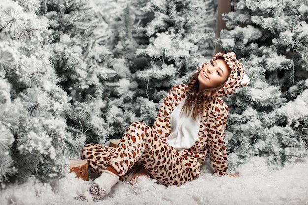 Lustige glückliche schöne frau mit einem lächeln in einem trendigen bärenpyjama nahe einem weihnachtsbaum mit schnee im studio