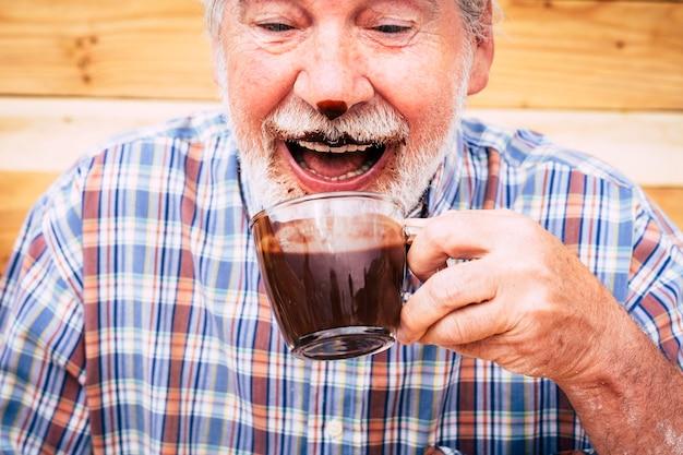 Lustige glückliche senioren kaukasischer alter mann, der heiße schokolade trinkt und es auf nase und bart hat - lachen und spaß haben - konzept der seniorität und fröhlicher älterer rentner