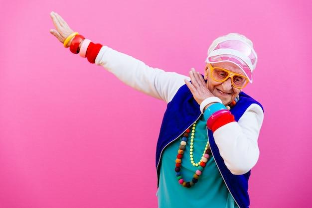 Lustige großmutterporträts. 80er jahre outfit. tupfen sie tanz auf farbigen hintergründen. konzept über dienstalter und alte menschen