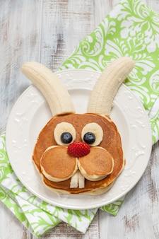 Lustige häschenpfannkuchen mit früchten für osterkinderfrühstück