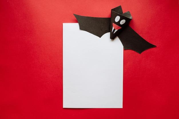 Lustige halloween-fledermaus aus papier auf einem roten hintergrund. postkarte auf helloween
