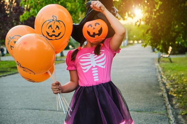 Lustige halloween-kinderkarnevalskostüme, die gesicht mit süßigkeitseimer im freien verstecken.